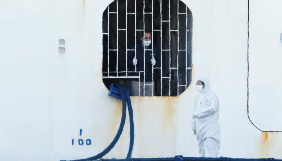 PÅ JOBB: En person som jobber som mannskap på Diamond Princess snakker med personell i smitteverndrakt på havnen i Yokohama. Foto: Kim Kyung-Hoon / Reuters / NTB scanpix