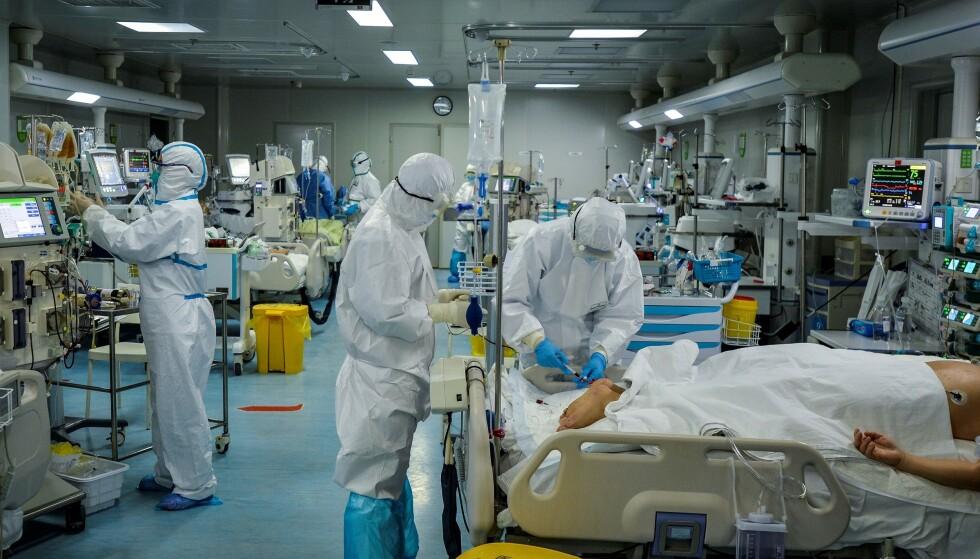 PÅ SYKEHUS: Bildet fra et sykehus i Wuhan i Kina viser hvordan helsearbeiderne er ikledd blant annet beskyttelsesfrakker, hansker og briller når de behandler covid-19-smittede pasienter. Også i Norge er det utarbeidet spesifikke råd til leger som må behandle smittede. Foto: STR / AFP / Scanpix