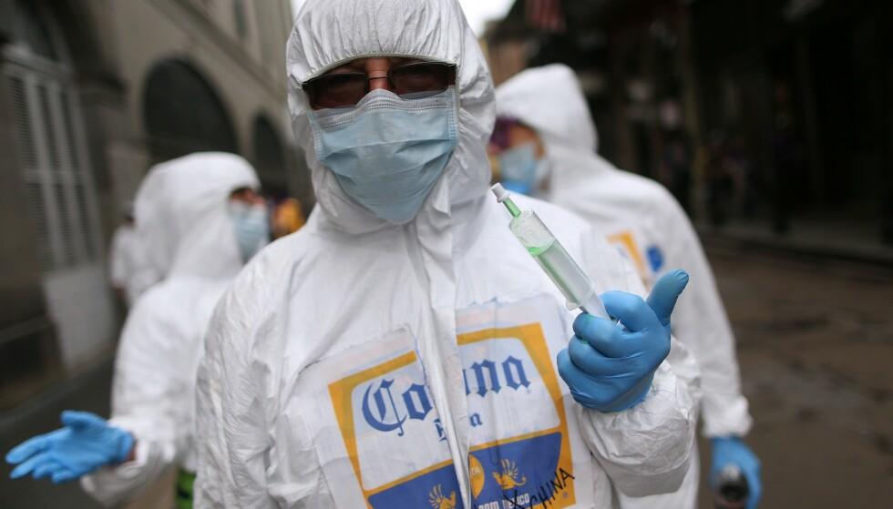 PROFETISK: Bildet fra årets Mardi Gras feiring i New Orleans ble langt mer aktuelt enn denne deltakeren kunne forutse eller ønske. Festdeltakeren var utkledd med beskyttelsesdrakt, ansiktsmaske og en stor vaksinesprøyte. Foto: AP/NTB Scanpix.