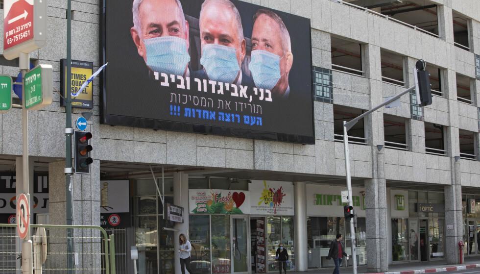 SKYLDER PÅ CORONA-SITUASJONEN: Europa har nå fått en diktator etter fullmakt i Ungarn, og i Israel har fungerende statsminister Benjamin Netanyahu begått et slags foreløpig statskupp med corona-situasjonen som begrunnelse, skriver innsenderne. Her sees statsminister Benjamin Netanyahu, Avigdor Lieberman og Benny Gantz på plakaten, med munnbind. Foto: Sebastian Scheiner/AP/NTB Scanpix