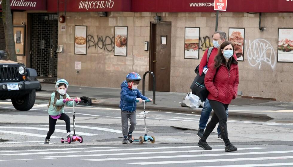 MYSTISK SYKDOM: En type mystisk bivirkning av det som kan være coronaviruset, er oppdaget hos barn i New York. Her leker to barn ute i byen sammen med foreldrene sine 25. april. Foto: Jamie McCarthy/Getty Images/AFP