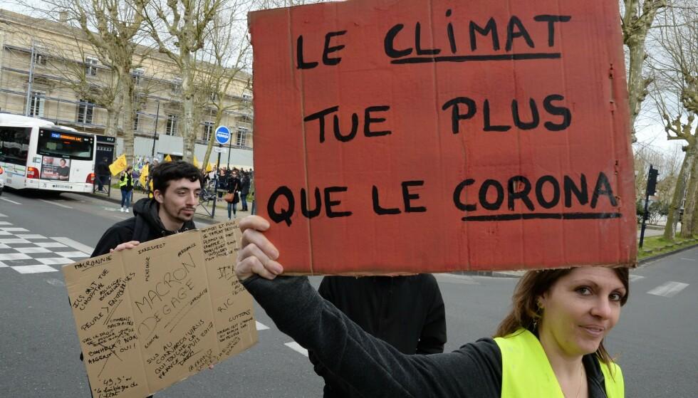 EN VEKKER: Demonstranter i Bordeaux holder en plakat som sier «klima dreper flere enn corona». Mange håper pandemien er en vekker som vil øke oppslutningen om klimatiltak. Foto: MEHDI FEDOUACH / AFP / NTB Scanpix