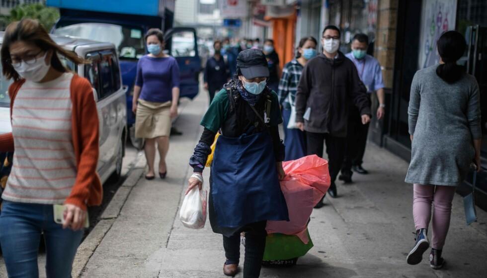 HONGKONG: En kvinne går langs Hong Kongs gater iført munnbind, som mange andre rundt henne. Bildet er tatt 27. mars 2020. Foto: Anthony WALLACE / AFP