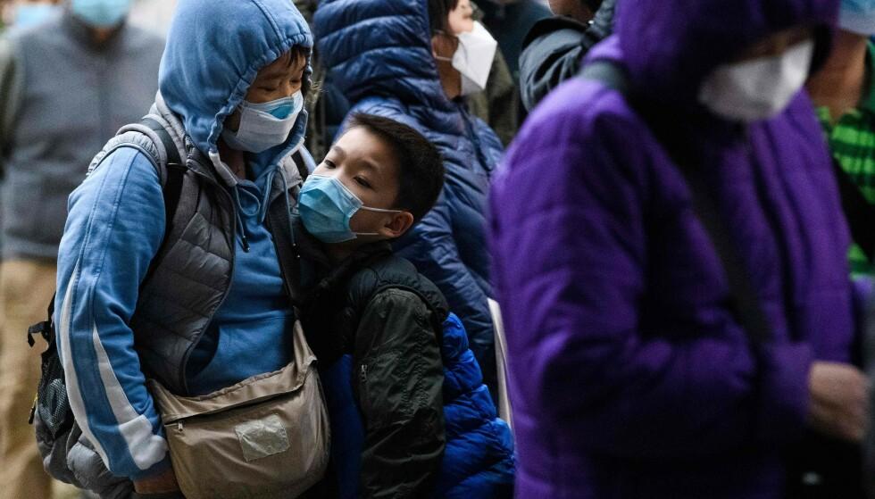 WUHAN: En ung gutt og en kvinne med munnbind i Wuhan, hvor eksperter mener coronaviruset oppstod, avbildet 5. februar 2020. Foto: Anthony WALLACE / AFP