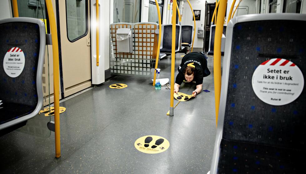 KLARGJØR: Monica Simonsen Ruud og Øyvind Korsell setter opp merking på T-banen i Oslo for å få riktig avstand mellom passasjerene. De bruker over to timer per togsett og klarer opp mot fe, sett hver natt. -Dette er tiltak for at passasjerene skal føle seg trygge. Foto: Nina Hansen / DAGBLADET