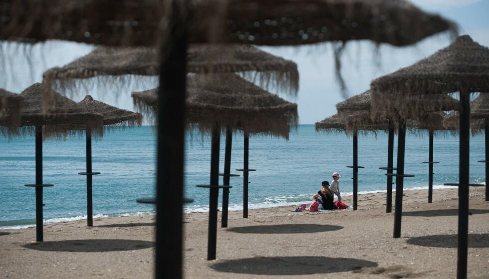 ØDE STRENDER: Etter 42 dager nesten innestengt kunne mor og barn gå ut på stranda La Malagueta i Málaga i Spania. Men der blir det ikke folksomt i sommer. Det er alle tiders krise i reiselivet sør i Europa. Foto: Jesus Merida / SOPA Images / Shutterstock / NTB Scanpix