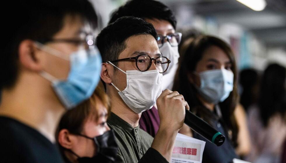 PROTESTERER: Nathan Law fra pro-demokratipartiet Demosisto snakker med pressen og deler ut løpesedler mot den nye kinesiske sikkerhetsloven fredag. Foto: Anthony Wallace / AFP / NTB Scanpix