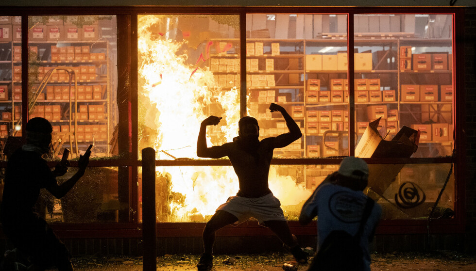 <strong>POSERER:</strong> En demonstrant poser foran en AutoZone-butikk som er satt fyr på onsdag kveld. Foto: AP