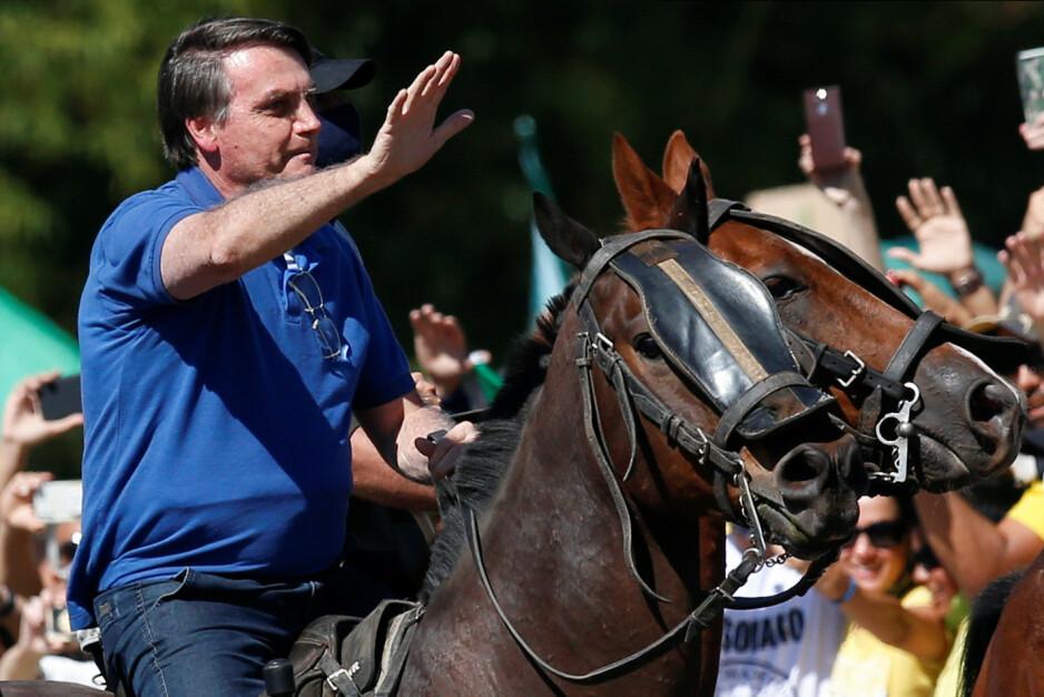 CORONA-STRID: President Jair Bolsonaro hilser fra hesteryggen tilhengere som demonstrerer til støtte for ham mens han er i strid med Høyesterett og avsatte statsråder. Han kjemper mot smitteverntiltak under epidemien. Foto: Ueslei Marcelino / Reuters / NTB Scanpix