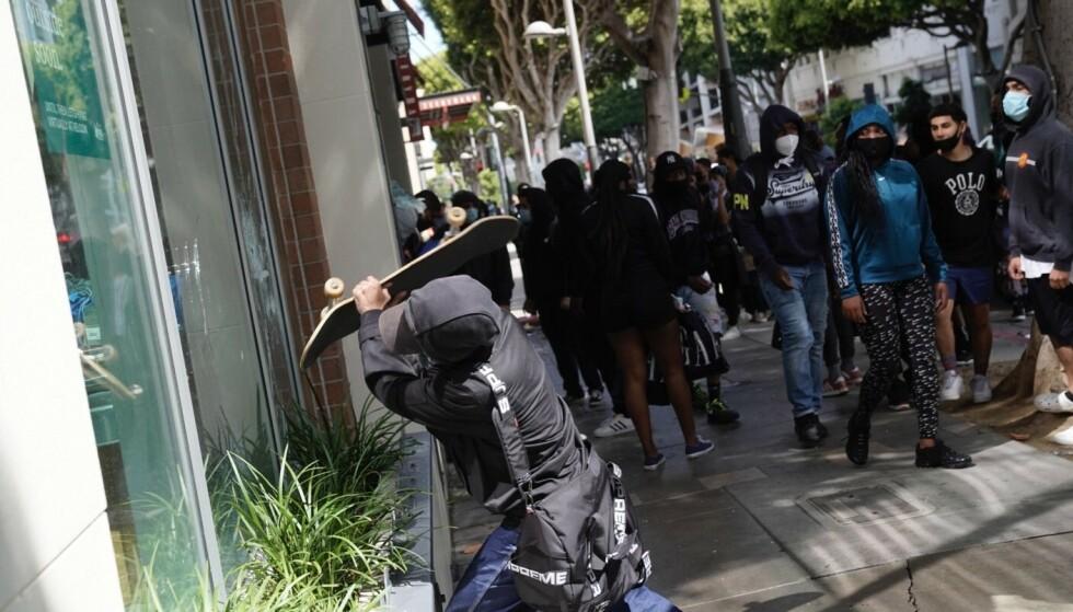 - TERRORISTER: En sortkledd og kamuflert demonstrant til angrep på et vindu i Santa Monica i California i pinsehelgen. Ifølge president Donald Trump en tilhgenger av terroristbevegelsen Antifa. Foto: Warrick Page, Getty Images/AFP/NTB Scanpix.