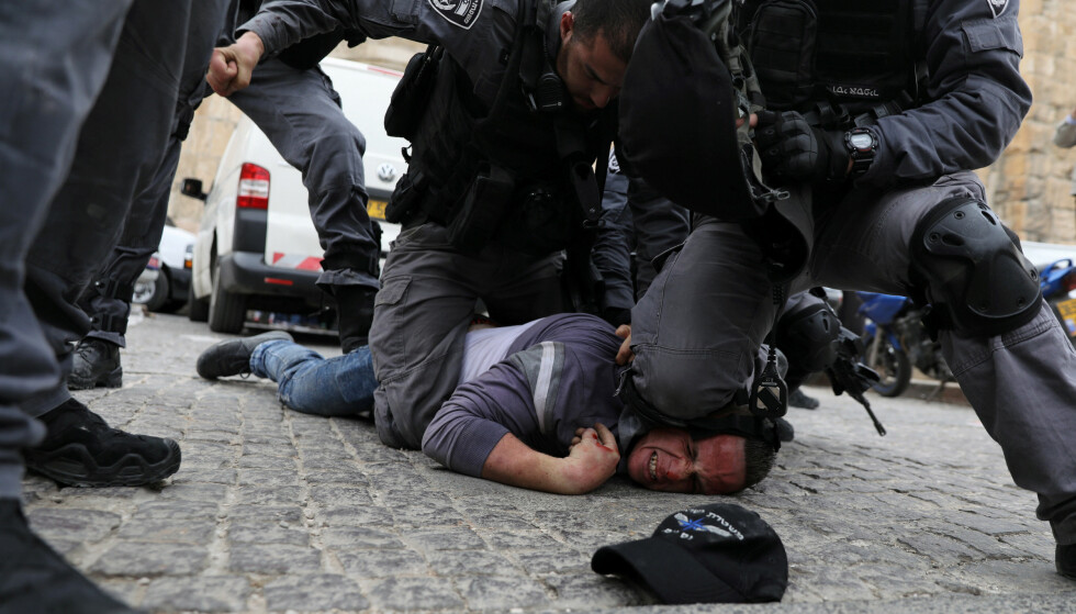 KNE MOT NAKKE-TEKNIKKEN: Bildet er tatt under urolighetene utenfor Al-Aqsa-moskeen i Jerusalem i mars i fjor, og viser tilsvarende grep som George Floyd ble utsatt for 25. mai i år i Minneapolis . Foto: Reuters