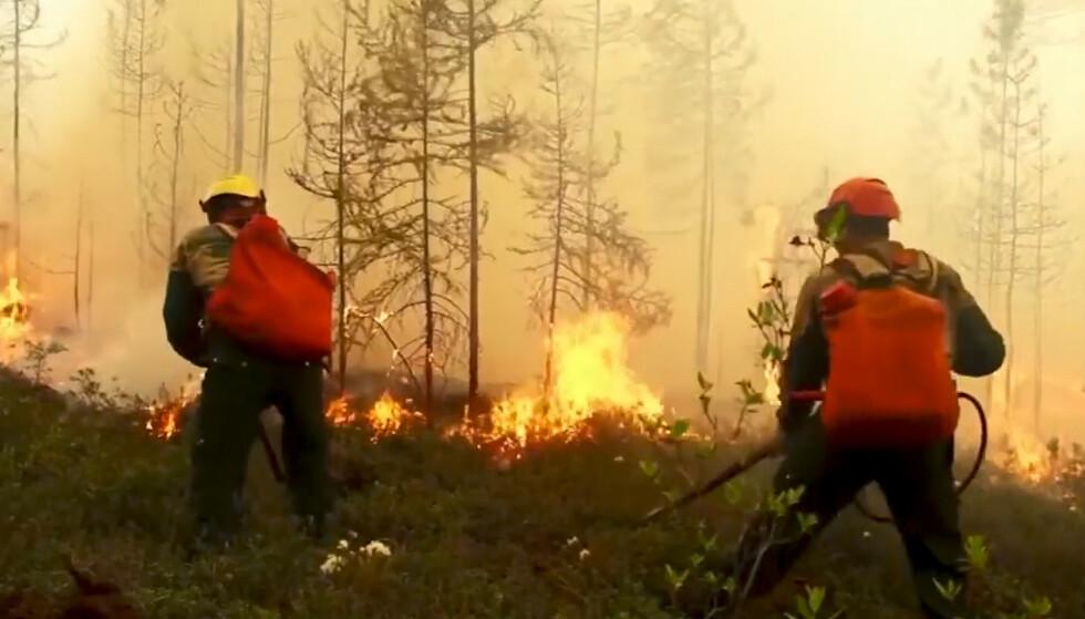 Russiske brannfolk kjemper mot flammene øst i Russland. Det anslås at branner i områder har sammenheng med høye temperaturer. Foto: RU-RTR Russian Television via AP / NTB scanpix