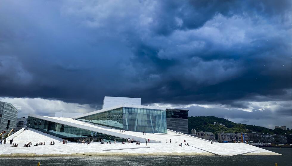 KAN BLI TORDEN: På Østlandet kan det bli kraftige regnbyger og torden den kommende uka. Akkurat hvor bygene vil treffe, er vanskelig å anslå, forteller meteorologen. Her henger mørke skyer over hovedstaden i juli 2020. Foto: Heiko Junge / NTB