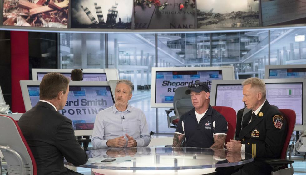 SKREMT: John Feal (nummer to fra høyre) overlevde 11. september, han beskriver frykten da han fikk påvist corona tidligere i år. Her er han i et TV-studio sammen med komiker Jon Stewart og tidligere nestkommanderende for brannvesenet i New York, Richard Alles. P Photo/Mary Altaffer