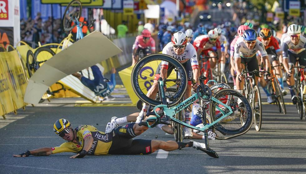 NESTEN FATALT: I bakgrunnen er Fabio Jakobsen (med blå drakt) på vei mot asfalten med hodet først, etter å ha blitt presset ut i reklameskiltene av konkurrenten Dylan Groenewegen. Fabio var nær døden i minuttenene etterpå. Etter en kort sesong med føle velt ser sykkelsporten igjen på mulighetene til å redusere antall stygge skader. FOTO: AP/Tomasz Markowski.