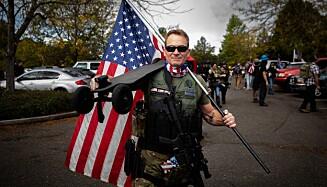 <strong>Armert:</strong> En deltaker på et Proud Boys møte i Delta Park, Portland, Oregon poserer for et bildet med gevær og det amerikanske flagget. Møtet ble avholdt av den høyreekstreme gruppen for vise sin støtte til president Donald Trump. Foto: AP/NTB.