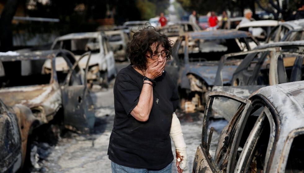 INFERNO: En kvinne finner hunden sin død i en utbrent bil, etter at Aten i Hellas opplevde et inferno av en skogbrann sommeren 2018. Foto: Costas Baltas / Reuters / NTB