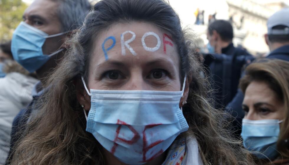 «LÆRER»: En demonstrant har ordet «lærer» tegnet i panna med fargene i det franske flagget. Demonstrasjonene søndag er til støtte for den drepte læreren Samuel Paty, og for å støtte opp om ytringsfriheten. Foto: AP Photo/ Michel Euler / NTB.