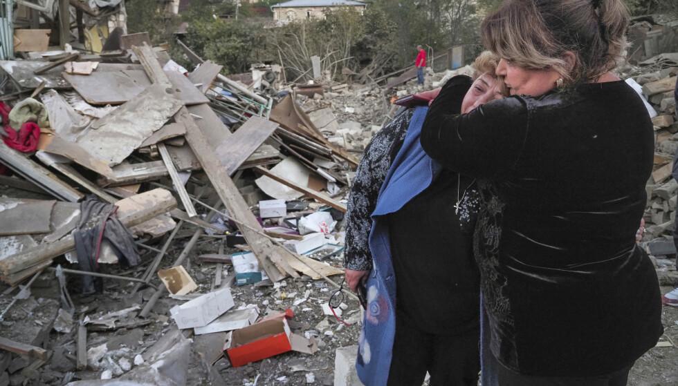 I GRUS: Lida Sarksyan (t.v.) fikk huset sitt i Nagorno-Karabakhs hovedstad Stepanakert totalt ødelagt etter et aserbajdsjansk artilleriangrep lørdag. Her trøstes hun av en nabo. Foto AP/NTB