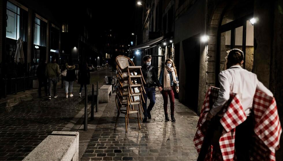 PORTFORBUD: Også i Frankrike har smittetallet gjort et markant hopp den siste tida. I Paris og åtte andre franske byer er det innført portforbud fra klokka 21 om kvelden til klokka 06 om morgenen. Her stenger en restaurant i den franske hovedstaden noen få minutter før portforbudet trer i kraft 17. oktober. Foto: Jeff Pachoud / AFP / NTB