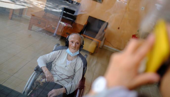 SKILT AV PLEKSIGLASS: Josefa Velasco (94) overlevde coronaviruset. Her snakker han med sin datter Cristina gjennom et pleksiglass satt opp på sykehjemmet i Barcelona. Denne typen besøk har blitt vanlig under coronapandemien for å bekytte de eldre. Foto: Nacho Doce / Reuters / NTB