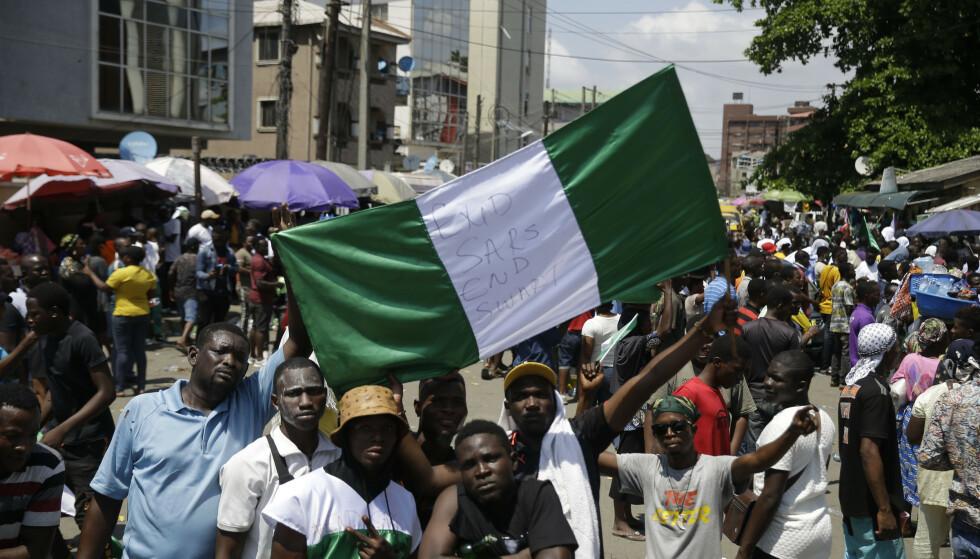 DEMONSTRER MOT POLITIVOLD: Demonstranter med det nigerianske flagget i Lagos tirsdag. Seinere samme kveld skal flere ha blitt skutt av militære styrker. Foto: Sunday Alamba / AP / NTB