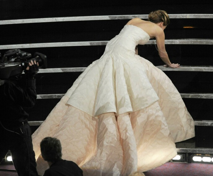 SNUBLET: Her ser man Jennifer Lawrence ta seg imot da hun snublet i trappa under Oscar-utdelingen i 2013. Foto: Chris Pizzello / Invision / AP / NTB