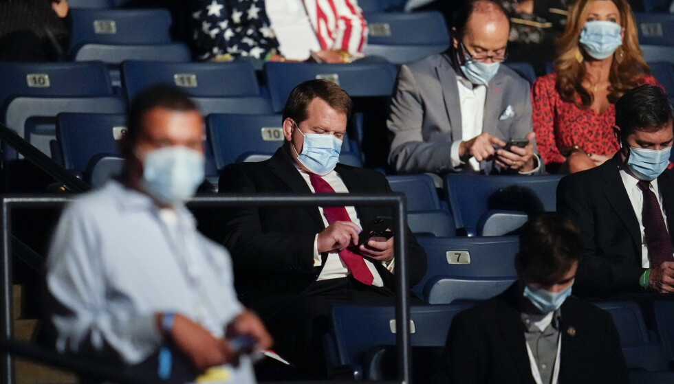 OVERRASKET: Tony Bobulinski kikker ned på mobilen kort tid før Joe Biden og Donald Trump gikk på debattscenen. Den tidligere løytnanten ble sluppet til offentligheten fra Trump-kampanjen bare timer før debatten. Foto: Julio Cortez / Ap / NTB