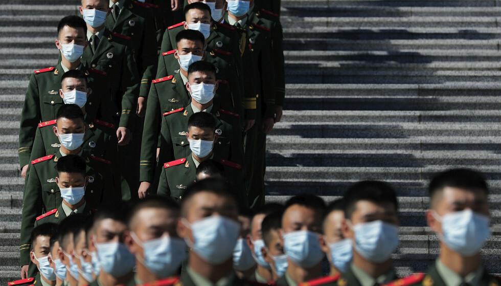 STRENGT: Siden januar har Nord-Korea strammet inn reglene for innbyggerne ytterligere, i frykt for coronaviruset. Her er nordkoreanske paramilitære politistyrker avbildet med munnbind fredag. Foto: Andy Wong / AP / NTB