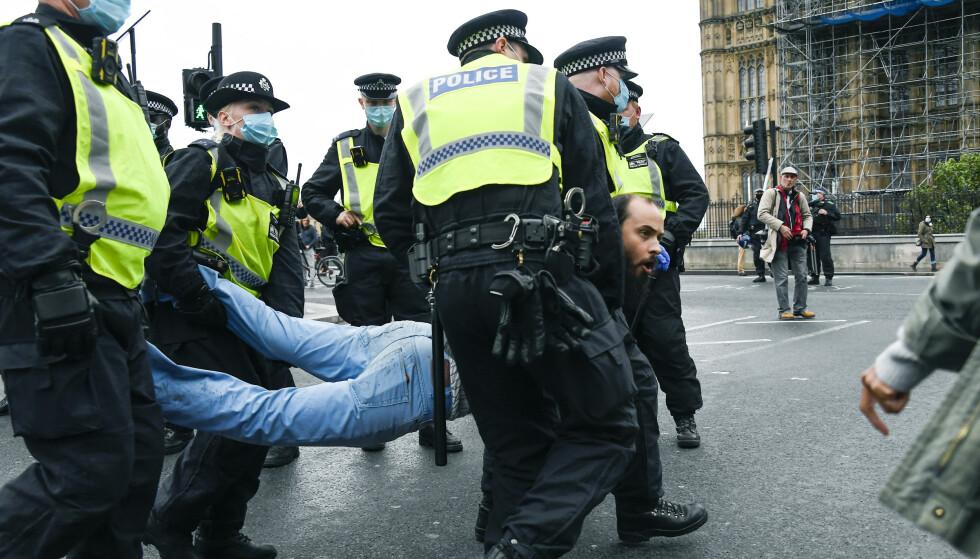 Police detain a man, during a coronavirus anti-lockdown protest on Westminster Bridge, in London, Saturday, Oct. 24, 2020. (AP Photo/Alberto Pezzali)