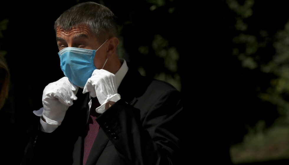 Tsjekkias statsminister Andrej Babis justerer på munnbindet sitt. Foto: Petr David Josek / AP / NTB