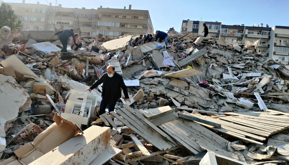 KOLLAPSET: Mange bygninger har kollapset etter at et stort jordskjelv rammet Izmir fredag ettermiddag. Foto: Mehmet Emin Menguarslan / Anadolu Agency/ ABACAPRESS.COM / NTB