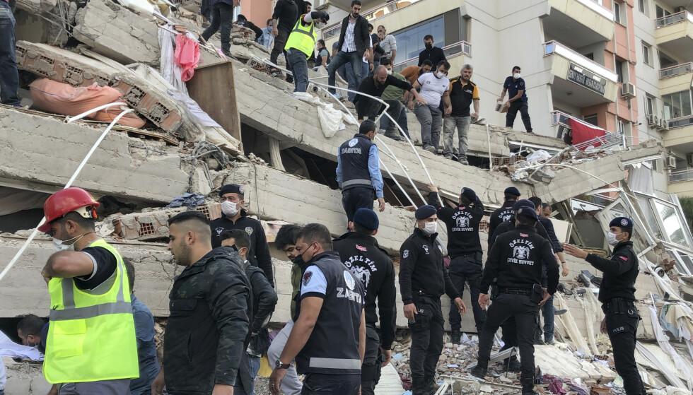 REDNINGSAKSJON: Redningsarbeidere og lokale prøver å redde de som sitter fast etter at bygningen har kollapset. Foto: AP Photo/Ismail Gokmen