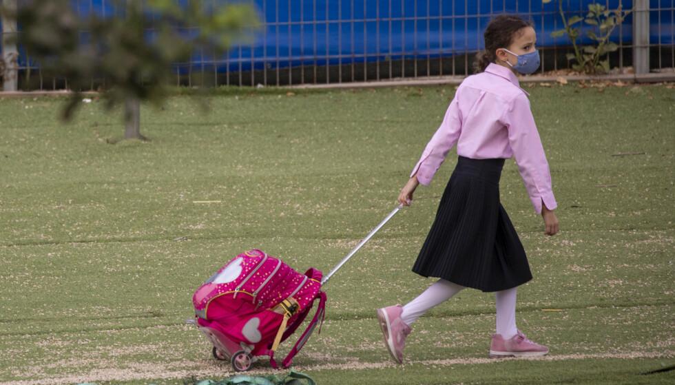 CORONA: En jente på vei til skolen som har sluppet opp etter lockdown. Foto: AP Photo/Ariel Schalit