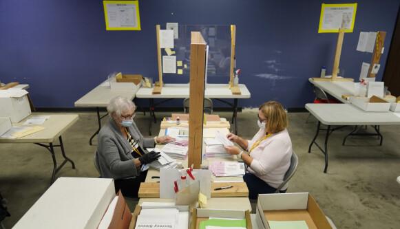 TELLER STEMMER: Delstatsansatte behandler poststemmer på et valgavdelingsanlegg i Clark County lørdag 31. oktober 2020 i Las Vegas. Foto: John Locker / AP