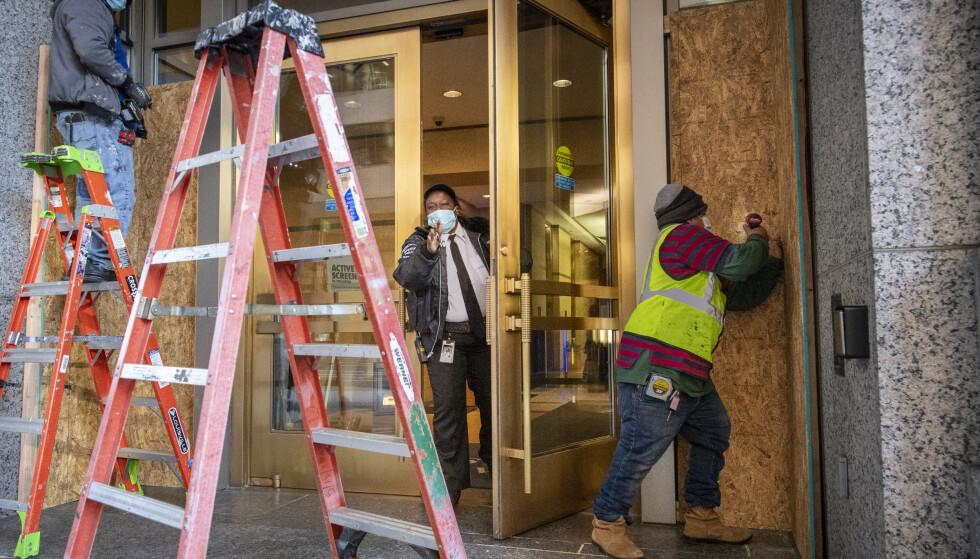 SKALKER: Det forventes opptøyer i Washington, D.C. i forbindelse med valget i morgen. Her skalker arbeidere vinduer med tjukke kryssfinerplater på et kontorbygg midt i sentrum av den amerikanske hovedstaden. Foto: Lars Eivind Bones / Dagbladet