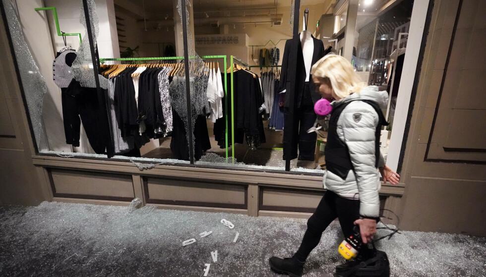 KNUST: En kvinne går over knust glass fra et ødelagt butikkvindu i Portland. Foto: AP / Marcio Jose Sanchez / NTB