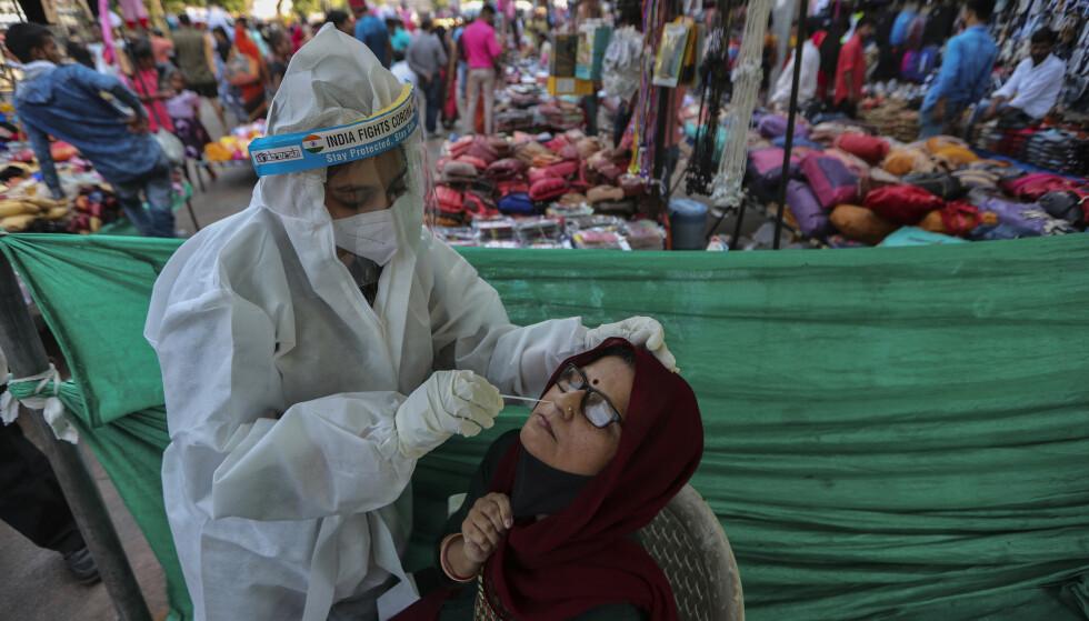 TESTES: En kvinne testes for coronaviruset på et marked i Ahmedabad, India, tirsdag. Foto: Ajit Solanki / AP / NTB