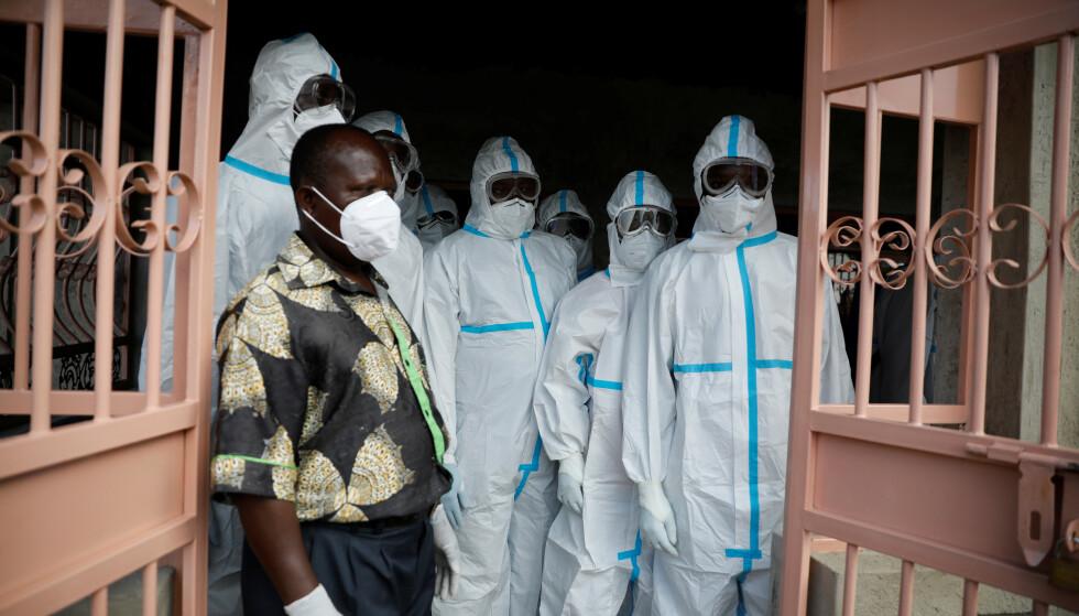 BEGRAVELSE: De som skulle bære kisten var ikledd fullt smittevernutstyr da de skulle følge den kenyanske legen Daniel Alushula til sitt siste hvilested i Khumusalaba, Kenya, fredag 13. november. Legen skal ha dødd av coronaviruset. Foto: Baz Ratner / Reuters / NTB
