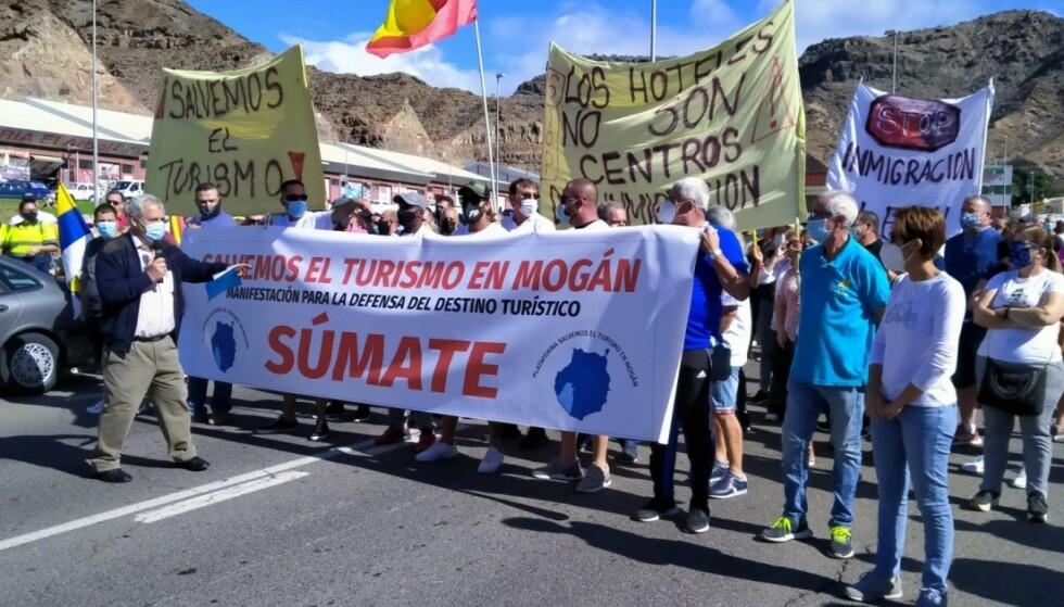 VIL HA MIGRANTER UT: Innbyggere i turistbyen Puerto Rico i Mogán kommune demonstrerte fredag mot at migranter bor på hotellene - angivelig på bekostning av byens turisme. Foto: Mogán kommune: