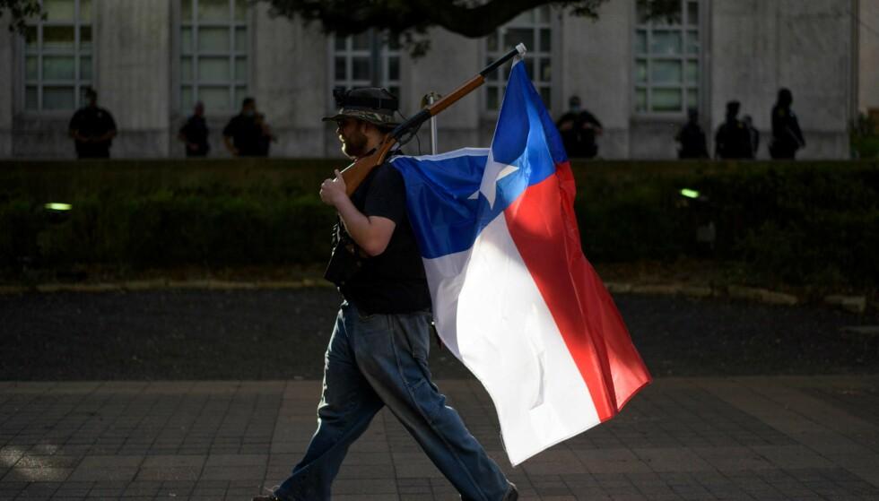 TEXAS: En mann med rifle og Texas-flagg. Illustrasjonsfoto: Mark Felix / AFP / NTB