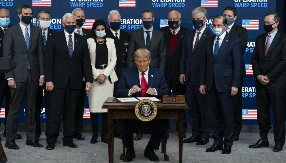 TRUMP TAPTE: USAs avtroppende president, Donald Trump, signerer en presidentordre om vaksinedistribusjon. Foto: AP Photo/Evan Vucci