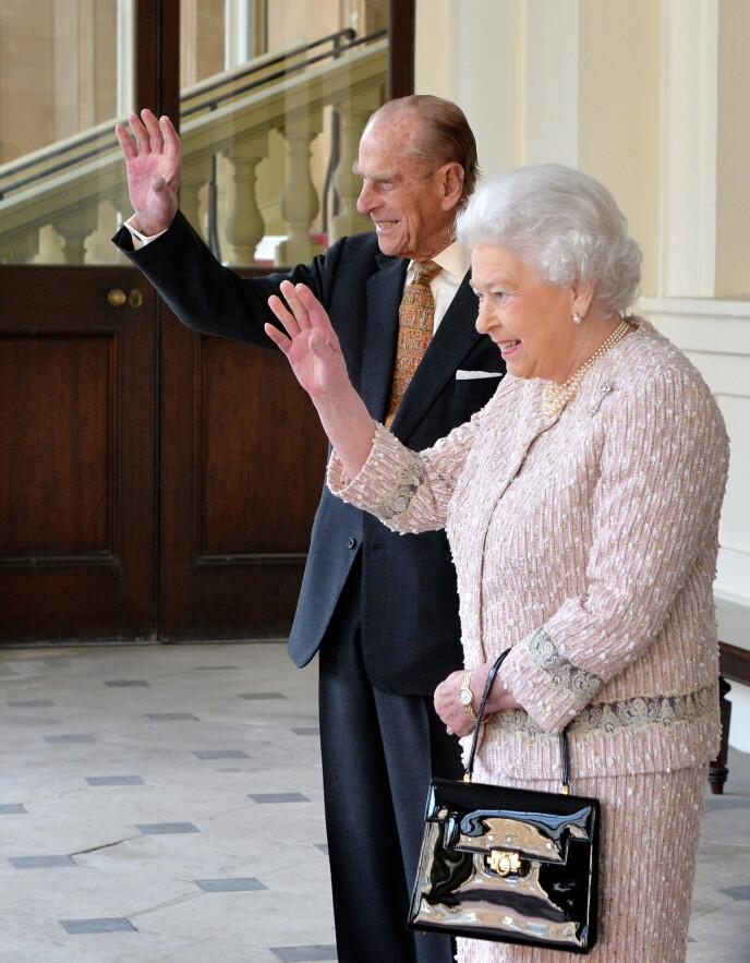 MYSTERIUM: Mange lurer på hvorfor dronninga alltid bærer veske. Det finnes det mange grunner til. Her avbildet med ektemannen, prins Philip, i 2015. Foto: REX / NTB
