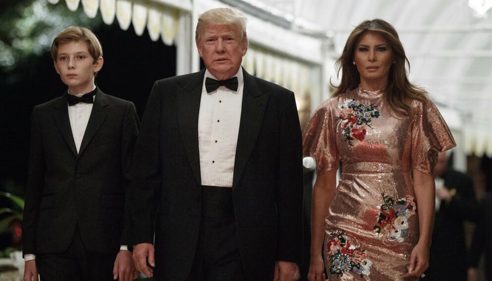 TRADISJONSRIKT: Donald Trump har arrangert nyttårsfest på Mar-a-Lago siden 2000, men i år reiser han lenge før fyrverkeriet skytes opp. Her er han fotografert med kona Melania og sønnen Barron på den tradisjonsrike festen i 2017. Foto: AP Photo/Evan Vucci, NTB