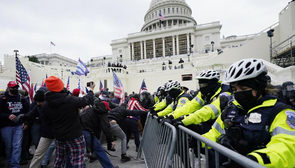 BRÅK: Trump-støttespillere prøver å komme seg gjennom barrikaden. Foto: AP Photo/John Minchillo