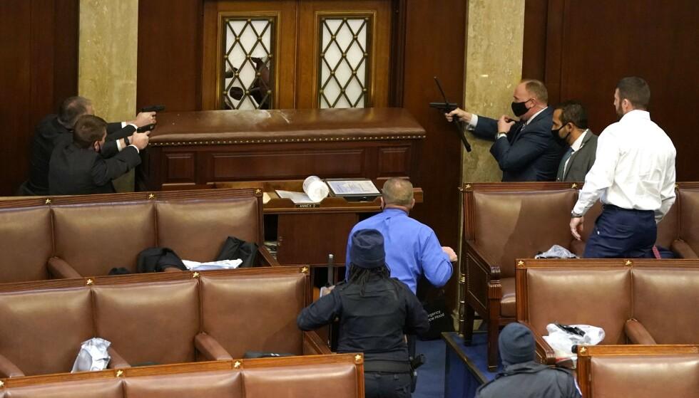 BEVÆPNET: Politi har trukket våpen ved inngangen til Representantenes hus, melder CNN. De sikter på en person som forsøker å nå frontdøren. Foto: Drew Angerer/Getty Images/AFP/NTB