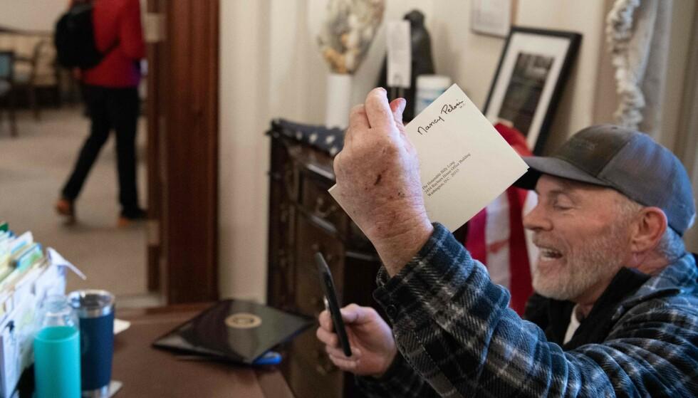 KONVOLUTT: Trump-tilhenger Richard Barnett hevder han la igjen 25 cent for konvolutten han tok fra Nancy Pelosis kontor. Foto: SAUL LOEB / AFP / NTB