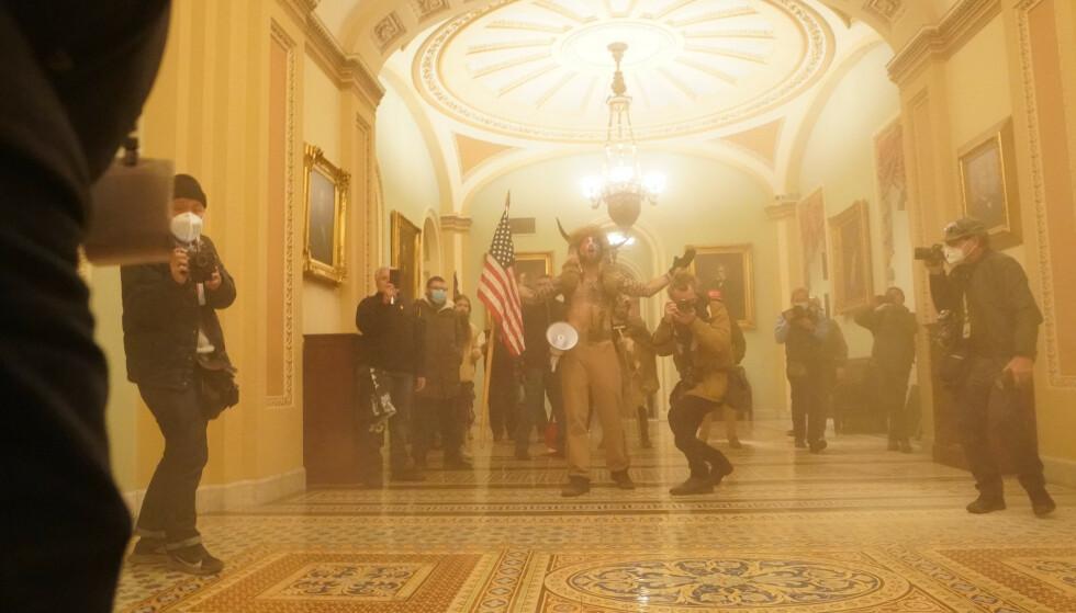 SJAMANEN: Mannen i forgrunnen, med pels trukket over hode og horn i panna, er identifisert som Jake Angeli, kjent som QAnon-sjamanen. Han var blant dem som ledet Trump-mobben, og tok seg helt inn i kammeret. Foto: Erin Schaff / New York Times