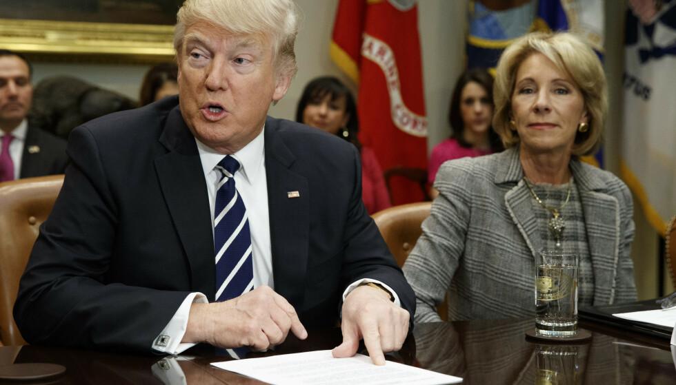 GIR SEG: Utdanningsminister Betsy DeVos har trukket seg i kjølvannet av opptøyene ved Capitol Hill. Her med president Donald Trump. Foto: AP Photo/Evan Vucci