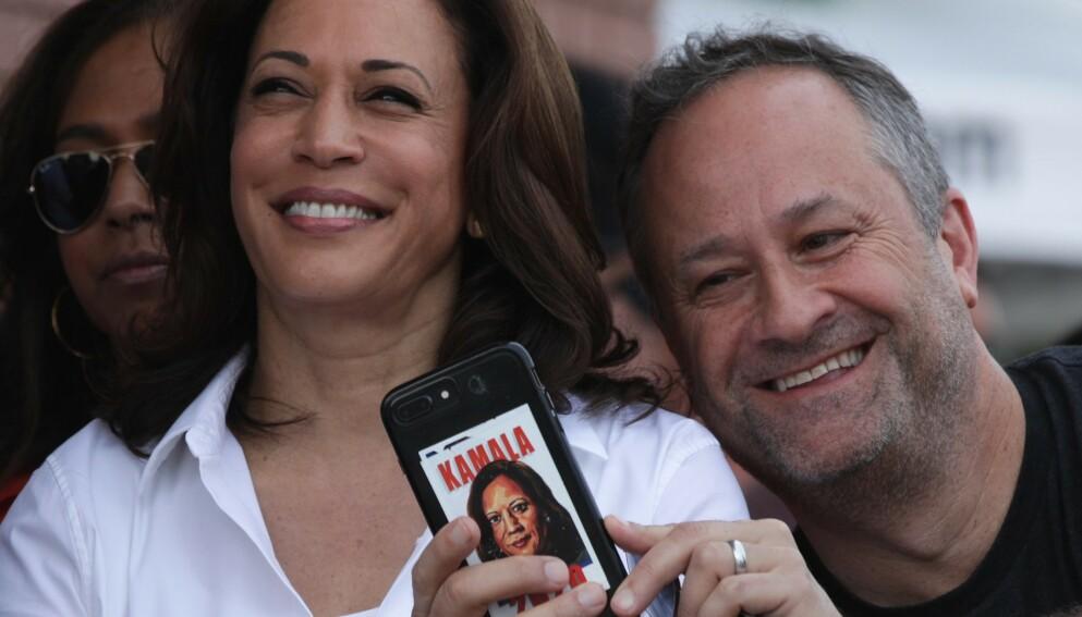 HEMMELIGHET: Kamala Harris (56) skal lenge ha holdt en liten hemmelighet skjult for ektemannen Doug Emhoff (56). Her er de avbildet sammen i 2019 - han med bilde av kona på telefonen. Foto: Alex Wong/ Getty Images/ AFP/ NTB